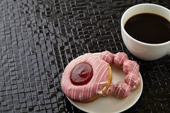 Tasse de café noir avec les butées toriques roses Photo libre de droits