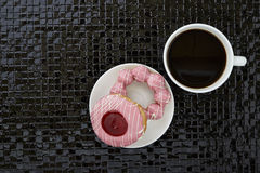 Tasse de café noir avec les butées toriques roses Image stock