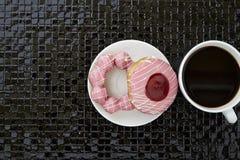 Tasse de café noir avec les butées toriques roses Photographie stock libre de droits