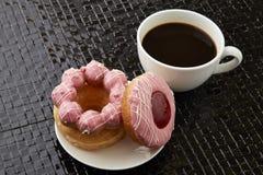Tasse de café noir avec les butées toriques roses Image libre de droits
