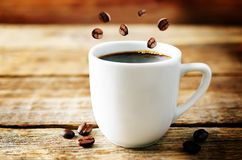 Tasse de café noir chaud avec des grains de café photographie stock
