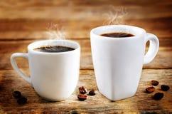 Tasse de café noir chaud avec des grains de café photos stock