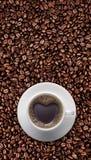 Tasse de café noir d'amour avec la forme de coeur sur le grain de café Photo libre de droits