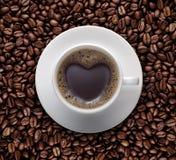 Tasse de café noir d'amour avec la forme de coeur sur le grain de café Images libres de droits