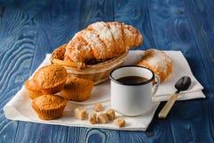 Tasse de café noir dans une vieille tasse d'émail, croissants o de petit déjeuner Images stock