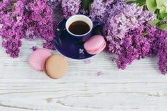 Tasse de café noir, de fleurs lilas et de macar français en pastel doux Photographie stock libre de droits