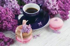 Tasse de café noir, de fleurs lilas et de macar français en pastel doux Images libres de droits