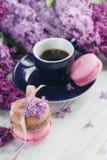 Tasse de café noir, de fleurs lilas et de macar français en pastel doux Photographie stock