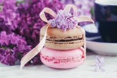 Tasse de café noir, de fleurs lilas et de macar français en pastel doux Photo libre de droits
