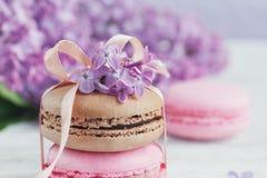 Tasse de café noir, de fleurs lilas et de macar français en pastel doux Photo stock