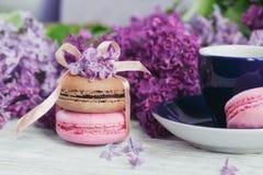 Tasse de café noir, de fleurs lilas et de macar français en pastel doux Image stock