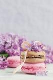 Tasse de café noir, de fleurs lilas et de macar français en pastel doux Photos stock
