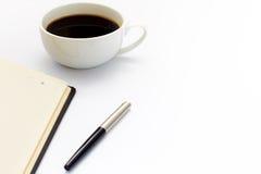 Tasse de café noir, de stylo et de journal intime sur le fond blanc concept minimal d'affaires Configuration plate Photos libres de droits