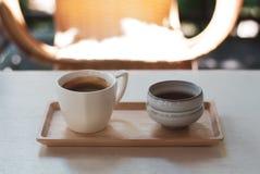 Tasse de café noire d'expresso avec le crema mince placé sur le plateau en bois avec le verre de thé photo stock