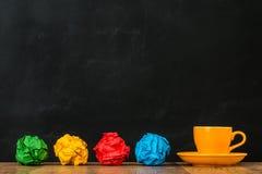 Tasse de café orange avec les boules de papier disposées Photos libres de droits