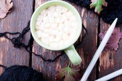 Tasse de café ou de chocolat chaud avec couvrant tricoté proche de guimauve et des aiguilles de tricotage Concept d'automne Noël  Photo stock