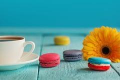 Tasse de café ou de thé avec la fleur et les macarons jaunes sur le fond bleu Images libres de droits