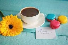 Tasse de café ou de thé avec la fleur et les macarons jaunes sur le fond bleu Photos libres de droits