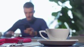 Tasse de café ou de thé sur la table, homme appréciant le petit déjeuner sur le fond banque de vidéos