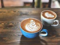Tasse de café de petite flûte d'art de latte et tasse de cappuccino sur la table en bois image libre de droits