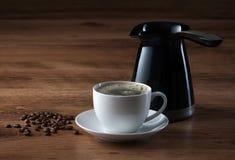 Tasse de café, pot de café et haricots sur la texture en bois Photographie stock libre de droits