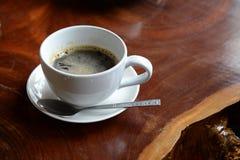 Tasse de café pour le petit déjeuner avec la cuillère sur la table en bois Image stock