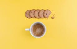 Tasse de café quelques biscuits sur une table jaune Photos libres de droits