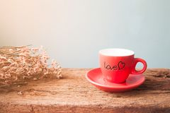 Tasse de café rouge avec AMOUR sur la table, le ` en bois d'amour et de Valentine Photo stock