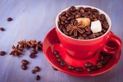 Tasse de café rouge avec des grains de café, des cubes en sucre et l'anis d'étoile Image stock