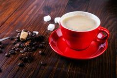 Tasse de café rouge avec des grains de café, des cubes en sucre et l'anis d'étoile Image libre de droits