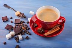 Tasse de café rouge avec des grains de café, des cubes en sucre et l'anis d'étoile Photographie stock