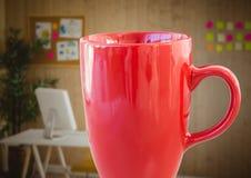Tasse de café rouge contre le bureau trouble Image stock