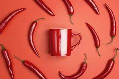 Tasse de café rouge entourée par des poivrons de piment sur un fond rouge Photographie stock libre de droits
