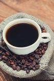 Tasse de café se tenant sur les grains Image stock