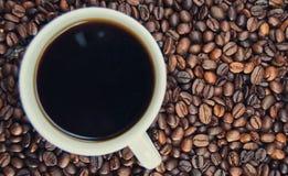 Tasse de café se tenant sur les grains Image libre de droits
