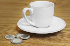 Tasse de café sur la pièce de monnaie de table Photo stock