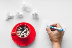 Tasse de café sur la soucoupe avec les guimauves, la main avec l'écriture de stylo sur une page de papier blanche et les feuilles Image stock
