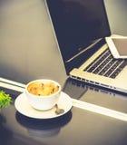 Tasse de café sur la table avec l'ordinateur portable et le téléphone intelligent Photo libre de droits