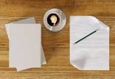 Tasse de café sur la table de fonctionnement avec le papier blanc et les livres Images libres de droits