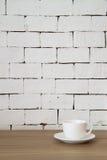 Tasse de café sur la table en bois avec le fond blanc de brique Images stock