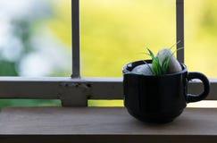 Tasse de café sur le plancher et le fond en bois de bokeh Photographie stock libre de droits