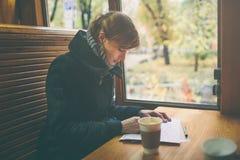 Tasse de café sur le premier plan avec la jeune femme élégante à la table en bois de boutique, gens d'affaires de pause, lumière  Images stock