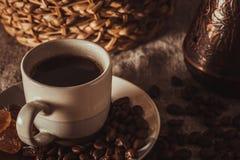 Tasse de café sur le textile avec des haricots, sucre foncé de sucrerie, pots, panier Images stock