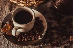 Tasse de café sur le textile avec des haricots, sucre foncé de sucrerie, pots, panier Image stock