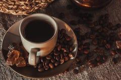 Tasse de café sur le textile avec des haricots, sucre foncé de sucrerie, pots, panier Photos stock