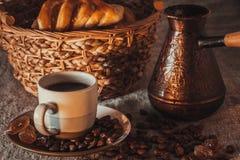 Tasse de café sur le textile avec les haricots, le sucre foncé de sucrerie, les pots, le panier et le gâteau Photos libres de droits