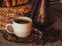 Tasse de café sur le textile avec les haricots, le sucre foncé de sucrerie, les pots, le panier et le gâteau Image stock