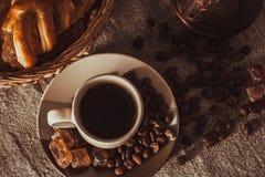 Tasse de café sur le textile avec les haricots, le sucre foncé de sucrerie, les pots, le panier et le gâteau Photos stock