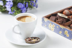 Tasse de café sur un fond blanc avec des un grand choix des chocolats dans une boîte en bois Image libre de droits