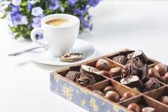 Tasse de café sur un fond blanc avec des un grand choix des chocolats dans une boîte en bois Images libres de droits